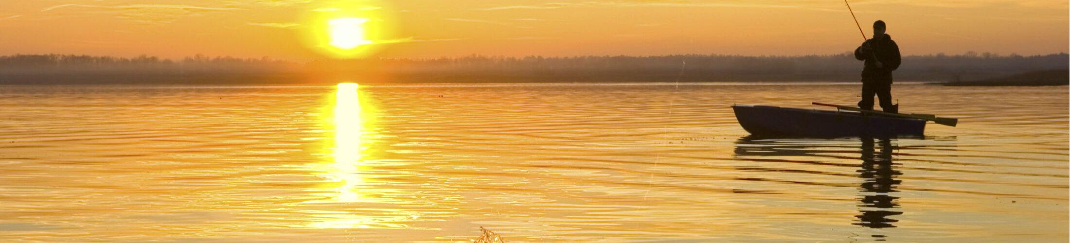 Main fishing on lake at sunset